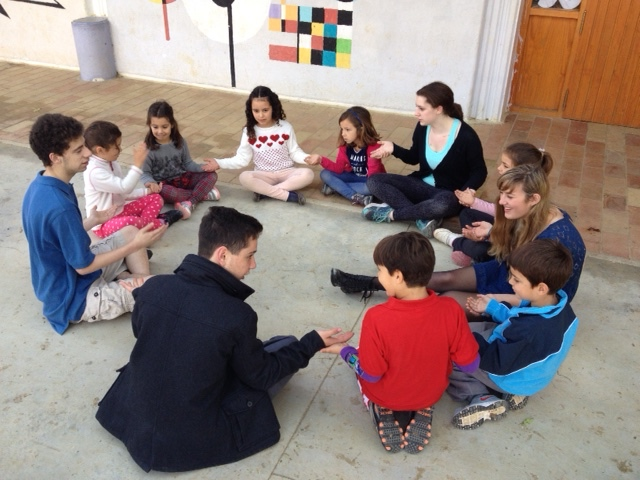 (Clockwise from top of photo) Jamie, Kami, Logan, and Paul teach some third graders a game in English.